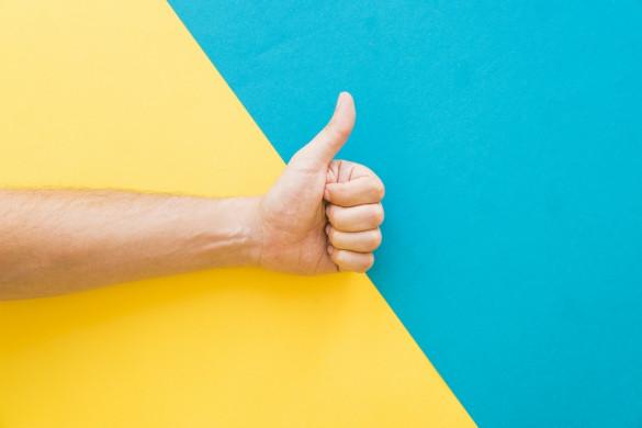 hand met opgestoken duim op een geel-blauwe achtergrond